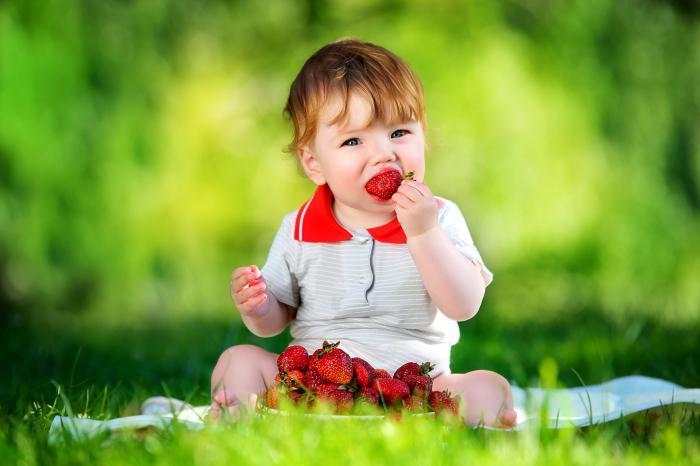Ребенок кушает клубнику